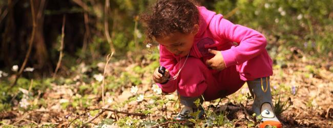 Fillette observant les feuilles avec une loupe